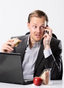 16467448-ocupado-hombre-de-negocios-muy-trabajador-almuerza-en-su-escritorio-mientras-trabaja-y-hablando-por-